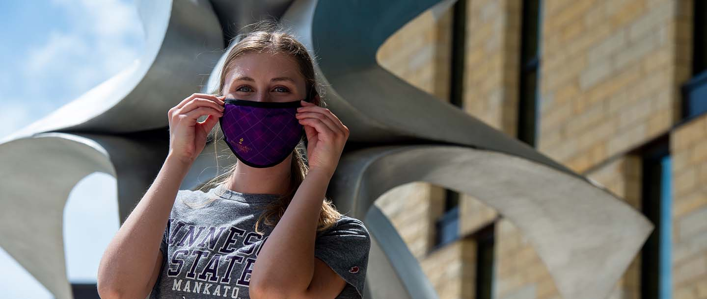 Student with mask near sculpture outside of the College of Allied Health and Nursing building