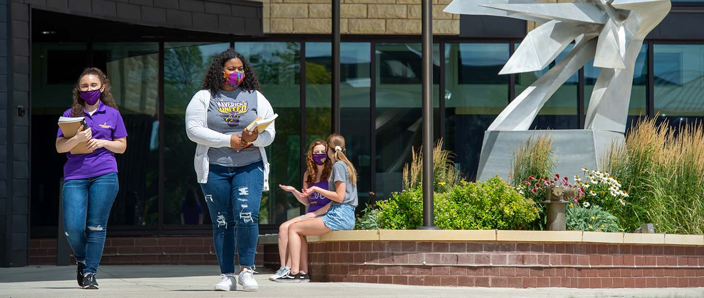 Students walking with mask in front of the College of Allied Health and Nursing building