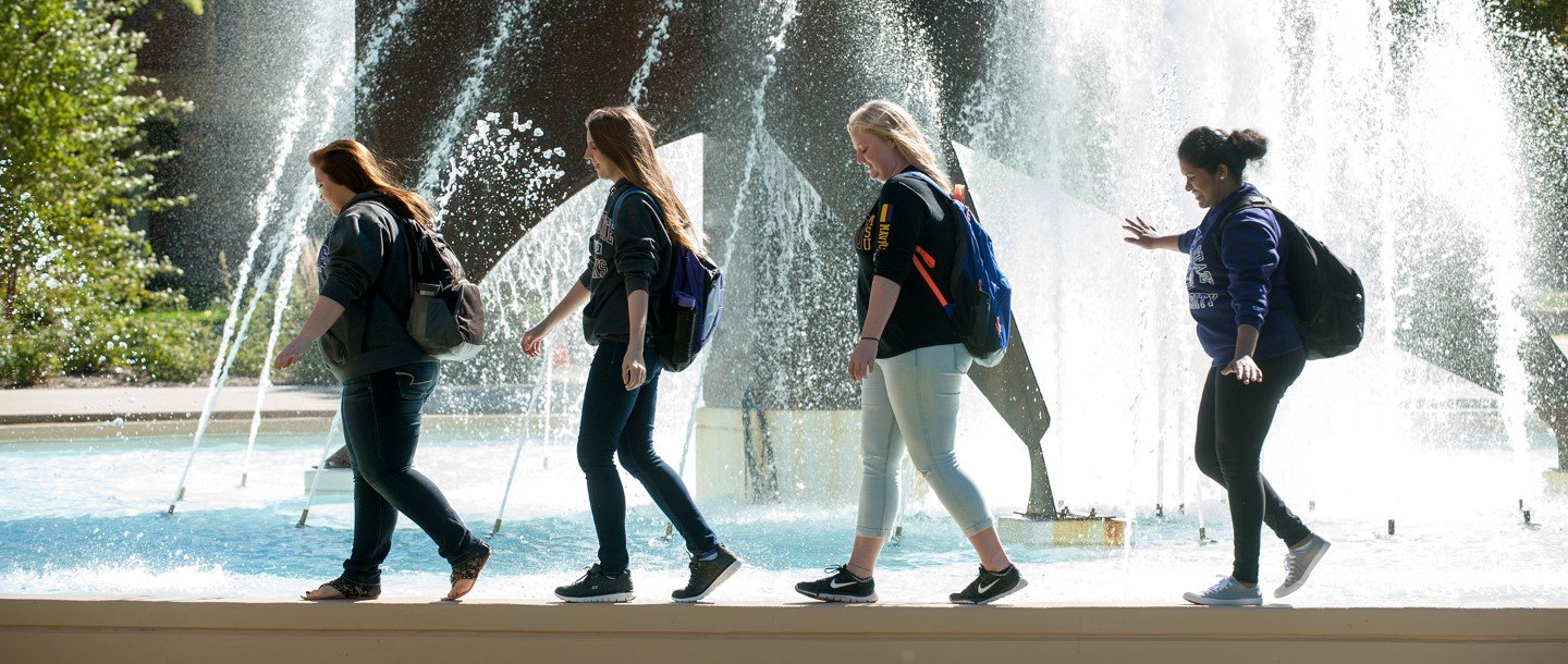 Students walking in front of fountain